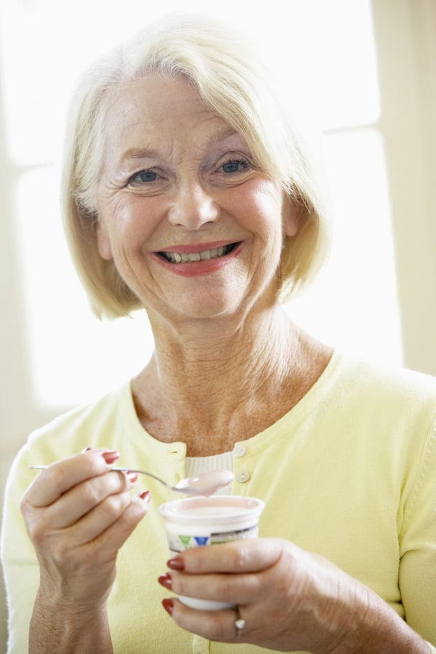 Senior woman eating yogurt
