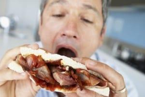 Man eating bacon sandwich