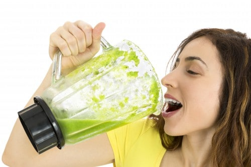 Girl drinking a green smoothie
