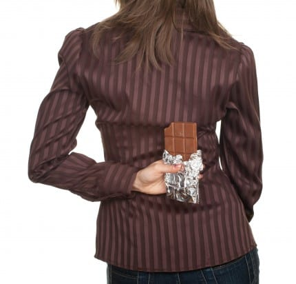 Woman holding chocolate behind her back