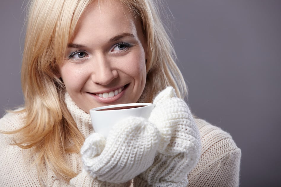 Warm girl drinking cocoa or coffee