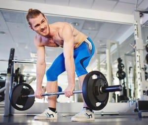 Portrait of strong sportsman lifting heavy weight in gym
