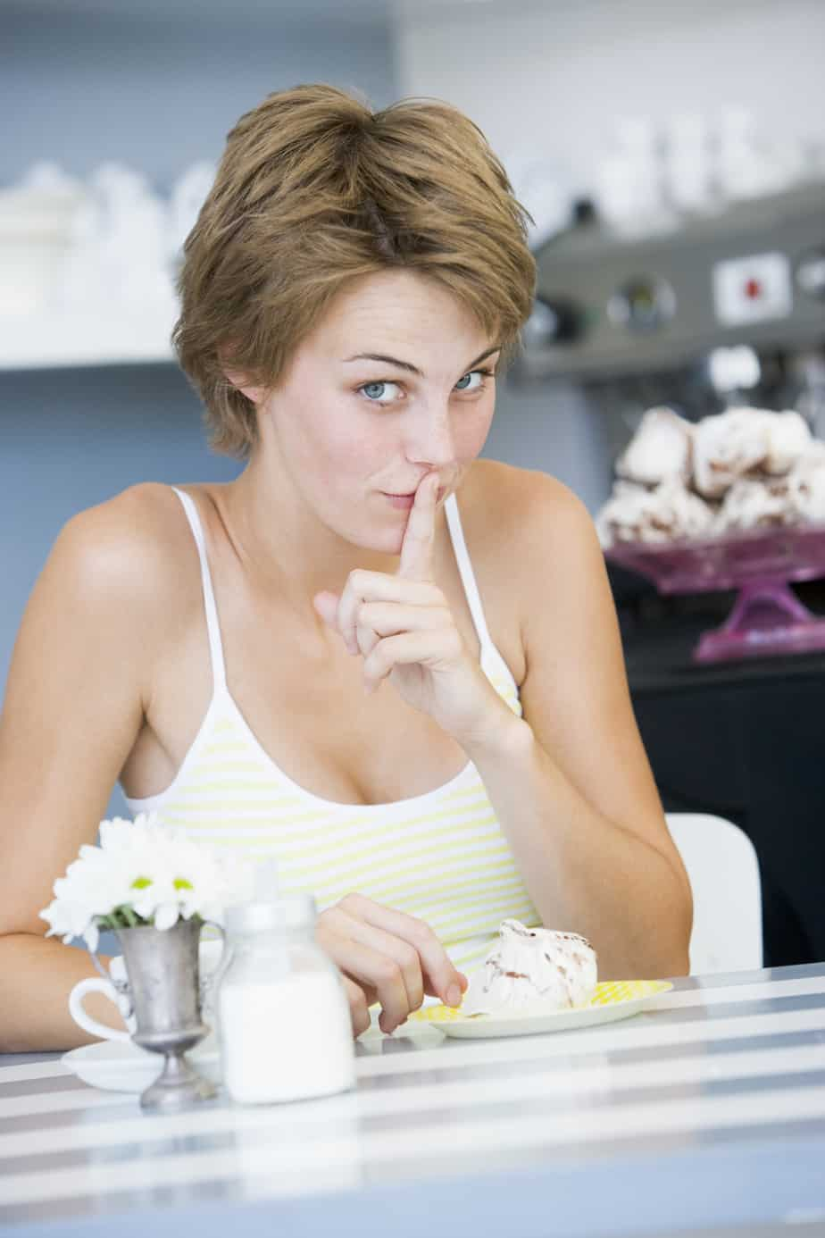 A young woman sitting in a cafe guiltily eating a sweet treat