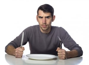 Man at dinner table with fork and knife raised.