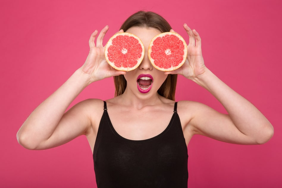 Joyful female with two half of grapefruit instead eyes