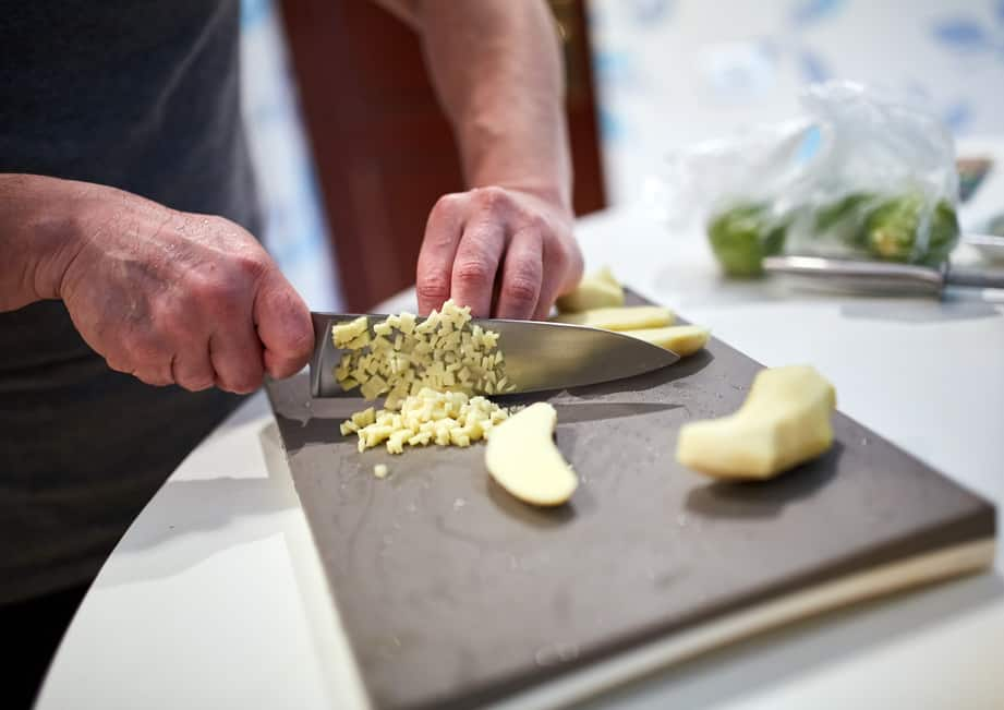 Chopping ginger on a board