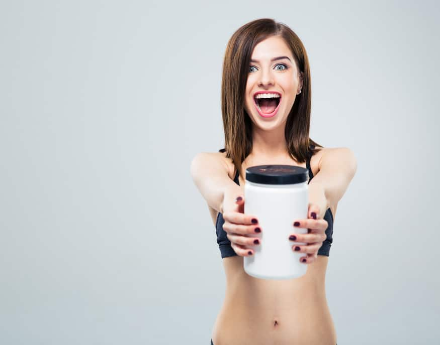 Cheerful smiling sporty woman with jar of protein