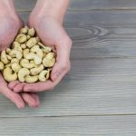 Woman showing handful of cashews in close up