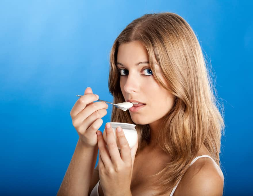 Healthy young woman eating yogurt