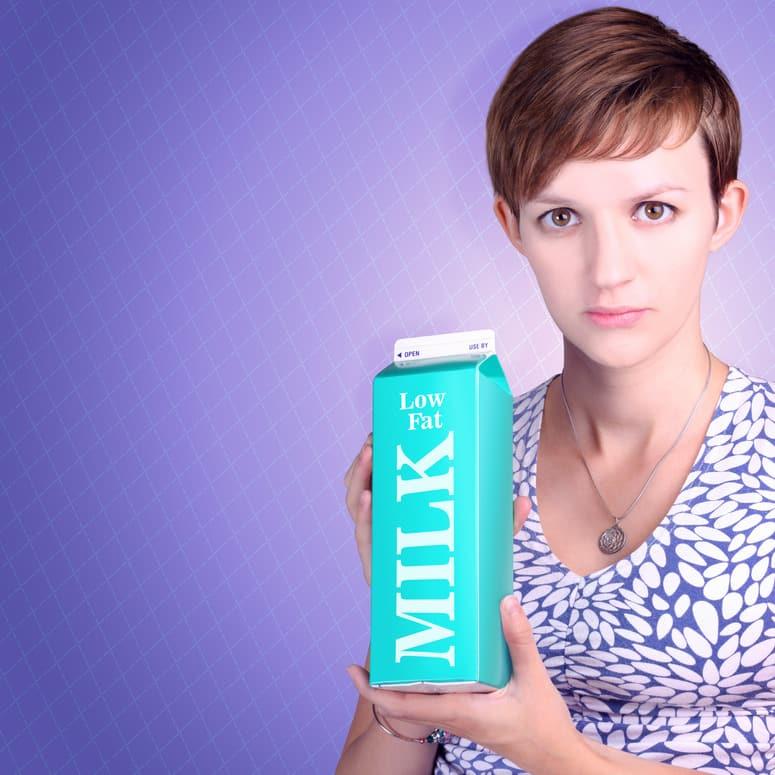 Serious woman holding low fat milk carton