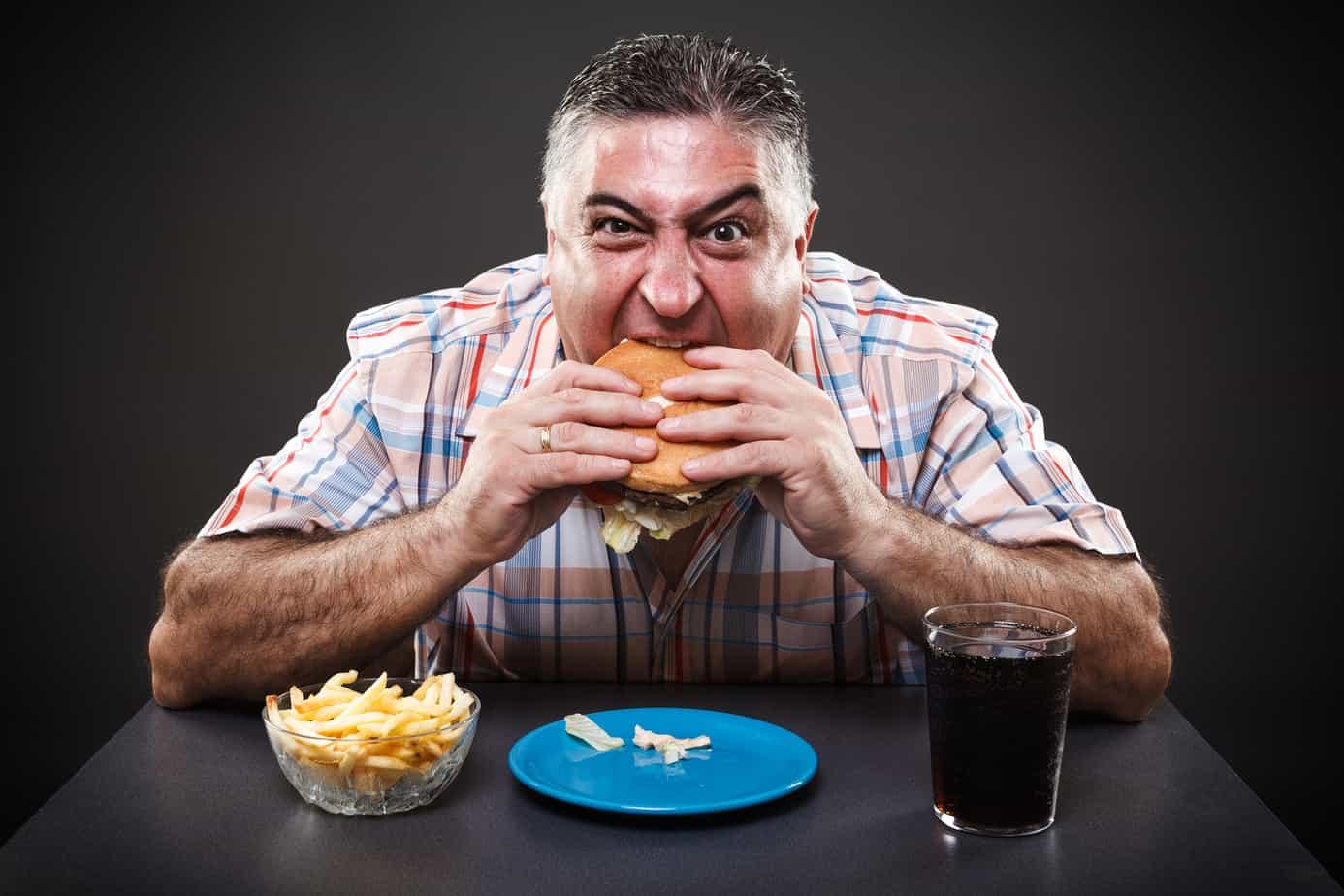 Greedy man eating burger
