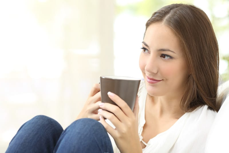 Young woman smiling with coffee