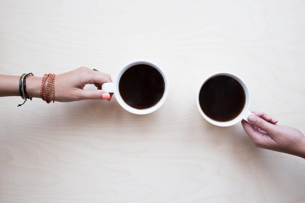 Two cups of coffee with hands